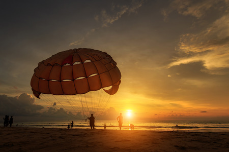 para: Silhouette of man is preparing para sailing at the sunset beach in Thailand Stock Photo