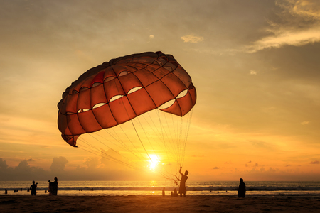 beach sun: Silhouette of man is preparing para sailing at the sunset beach in Thailand Stock Photo