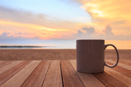 Close up coffee cup on wood table at sunset or sunrise beach Stok Fotoğraf - 46971406