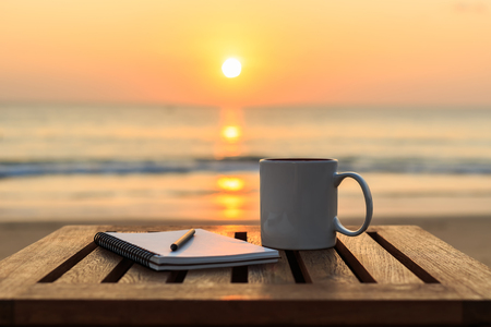 Close up coffee cup on wood table at sunset or sunrise beach