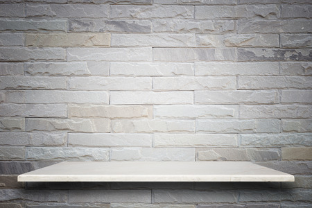 Empty top of natural stone shelves and stone wall background. For product display