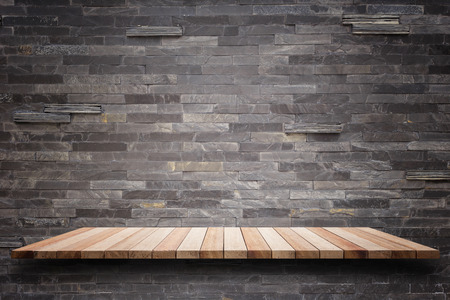 product placement: Empty top wooden shelves and stone wall background. For product display