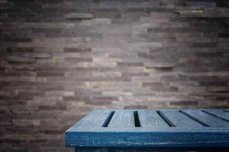 room background: Empty top wooden table and stone wall background. For product display