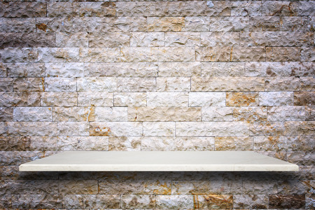 stone: Empty top of natural stone shelves and stone wall background. For product display