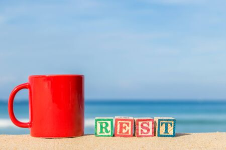 rest: word REST in colorful alphabet blocks and coffee cup on tropical beach, Phuket Thailand