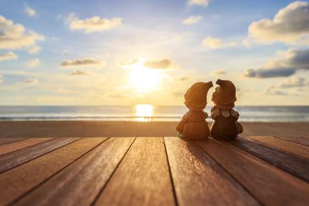 sunset: Cierre de dos muñecos sentado en la mesa de madera en la playa de la puesta del sol