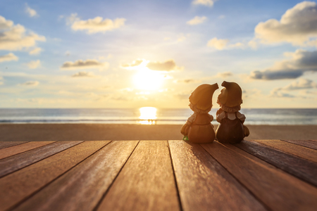 dolls: Close up two dolls sitting on wooden table at sunset beach Stock Photo