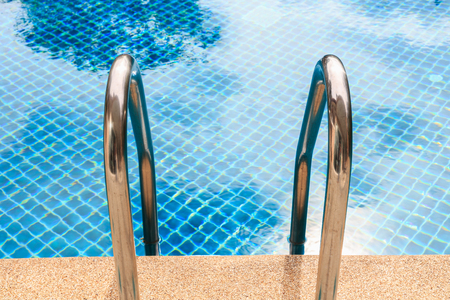 stainless: Outdoor swimming pool with shiny stainless steel stair