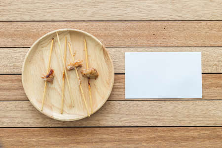 bamboo stick: Top view empty bamboo stick of grilled pork and paper note on wooden dish