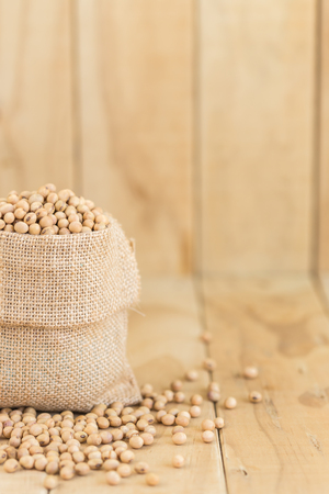soja: Close up soy beans in sack on wooden desk
