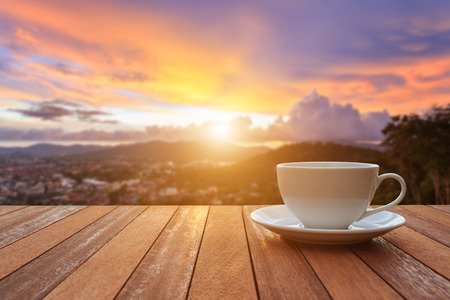 Close up white coffee cup on wood table and view of sunset or sunrise background
