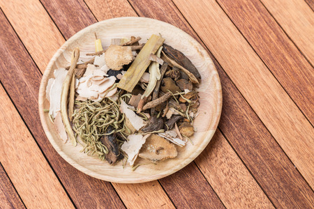 codonopsis roots: Mix of chinese herbal medicine in wooden dish on wood plank background