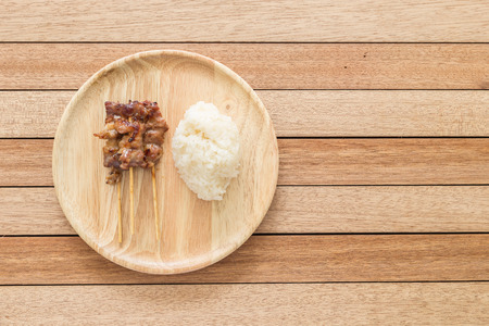 bamboo stick: Top view grilled pork with bamboo stick and Thai sticky rice on wooden dish