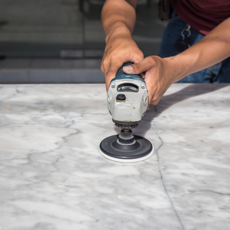 Man polishing marble stone table by small angle grinder Stok Fotoğraf