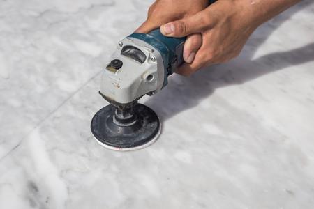 Man polijsten marmeren stenen tafel door kleine haakse slijper Stockfoto