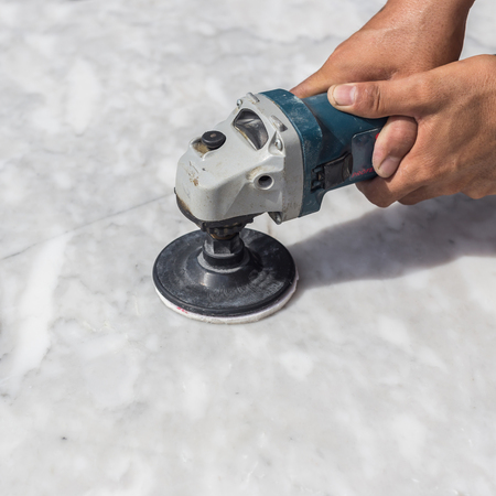 polishing: Man polishing marble stone table by small angle grinder Stock Photo