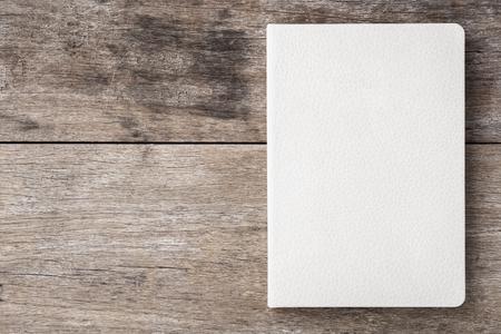 portadas: Vista superior del libro blanco sobre fondo antiguo tablón de madera