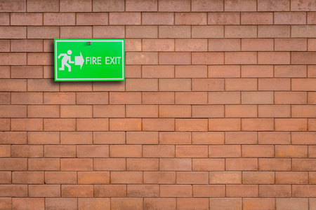 direction sign: Green fire exit sign on stone wall background Stock Photo