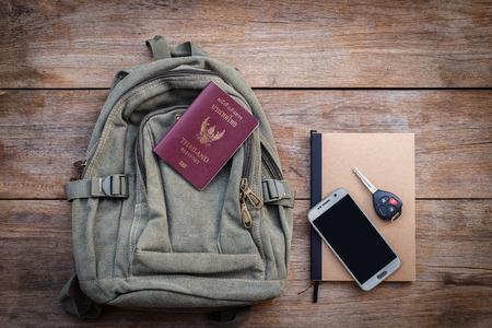 mochila de viaje: Vista superior Tailandia pasaporte, mochila, teléfono inteligente, la llave del coche y el libro sobre fondo de madera del tablón