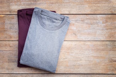 Top view of color T-Shirt on grey wood plank background Foto de archivo