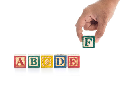 red building blocks: Colorful wood alphabet blocks and hand holding F isolated on white background