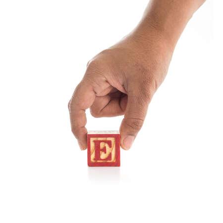 alphabet blocks: Hand holding colorful alphabet blocks E isolated on white background Stock Photo