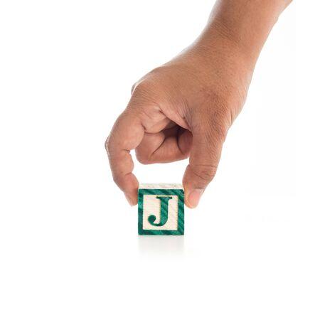 alphabet blocks: Hand holding colorful alphabet blocks J isolated on white background