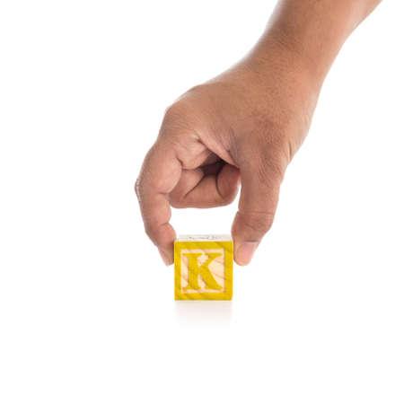 alphabet blocks: Hand holding colorful alphabet blocks K isolated on white background