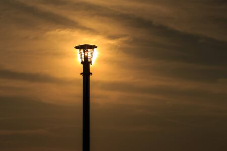 lamp on the pole: Silhouette of lamp pole on sun and sky background
