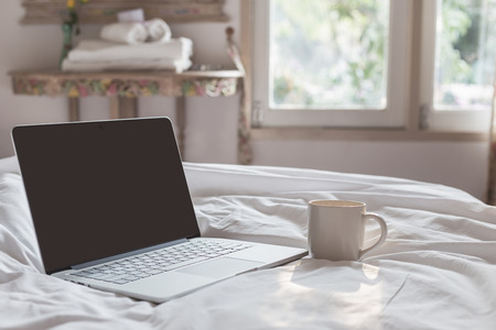 Coffee cup and laptop on the bed in morning time, focus on cup