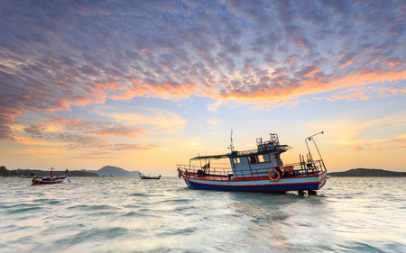 kata: Fishing boat stand at sunrise beach in Phuket, Thailand
