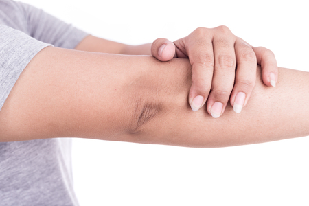 Close up womans hand holding her elbow isolated on white background. Elbow pain concept.