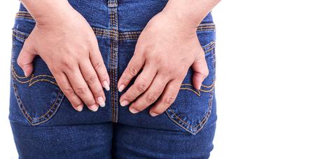 Fermez la main de femme tenant le dos isolé sur fond blanc: les hémorroïdes Concept Banque d'images