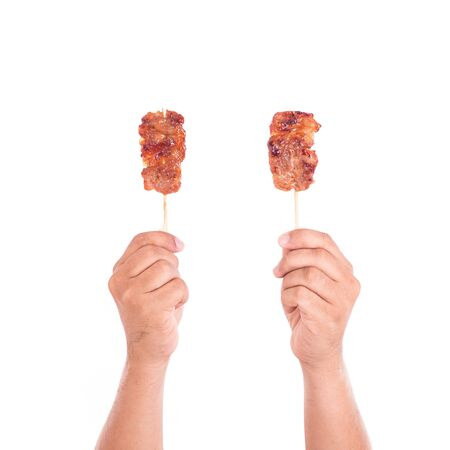 pork: Hand holding grilled pork in bamboo stick isolate on white background