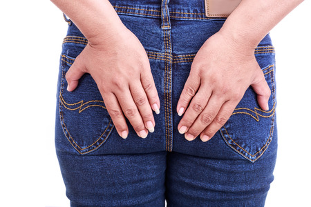 Close up woman's hand holding the backside : Concept hemorrhoids