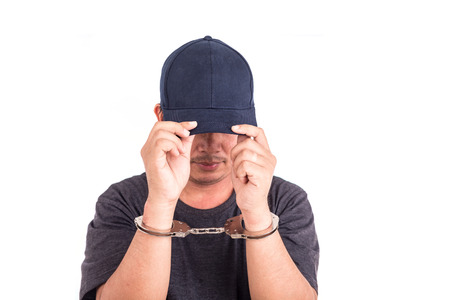cuffed: Close up man with handcuffs on hands isolated on white background
