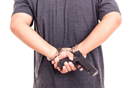 cuff bracelet: Close up man with handcuffs and gun on hands isolated on white background Stock Photo