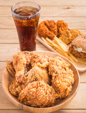 Close up fried chicken, french fries and soft drink on wooden table