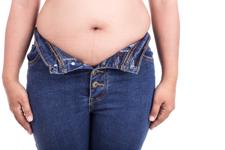 paunch: Close up fat woman trying to wear jeans : Fat and Healthy concept Stock Photo