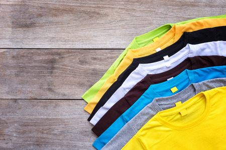Top view of color T-Shirt on grey wood plank background Archivio Fotografico