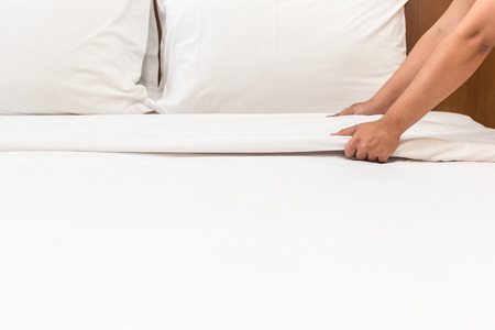 Close up hand set up white bed sheet in hotel room Фото со стока