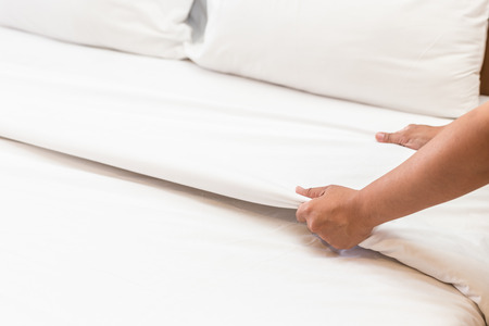Close up hand set up white bed sheet in hotel room Stock Photo