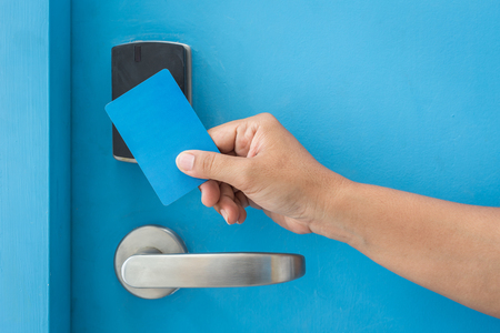 keycard: Close up hand holding blue hotel keycard in front of electric door