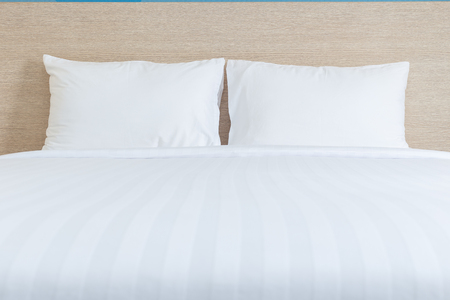 white pillow: Close up white bedding sheets and pillow in hotel room Stock Photo