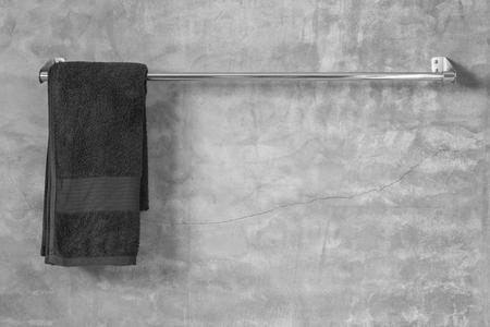 화장실에 갈색 수건 회색 시멘트 벽에 스테인레스 스틸 수건