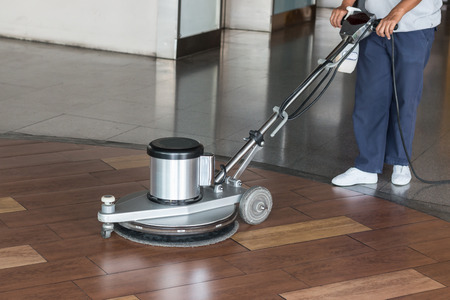 office floor: Woman worker cleaning the floor with polishing machine