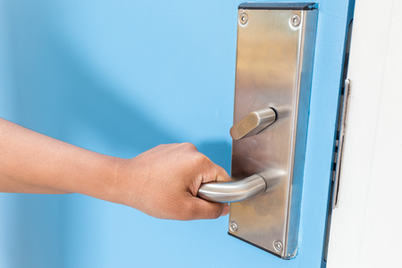keycard: Close up hand holding on stainless steel door handle in hotel