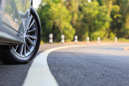 Close up front car wheel on the asphalt road