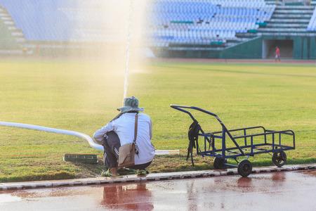 sprinkle system: A unidentified people preparing big sprinkler spray water to grass field in football stadium Stock Photo