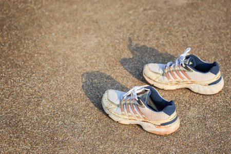 whitem: Old pair of sports shoes standing on a tartan race track
